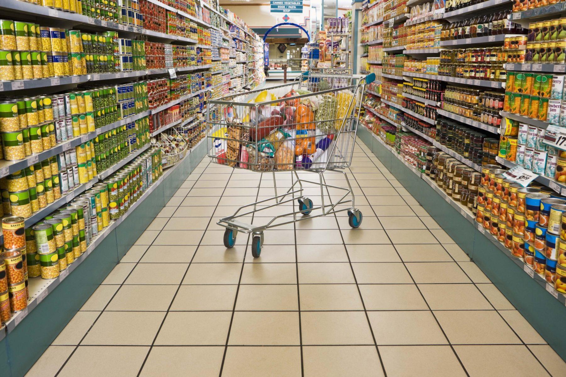 Carrello per la spesa in mezzo al corridoio del supermercato